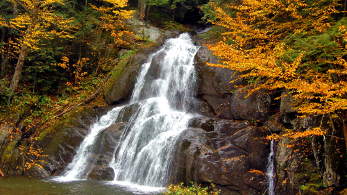 Waterfall in Rocks and Autumn Trees Around